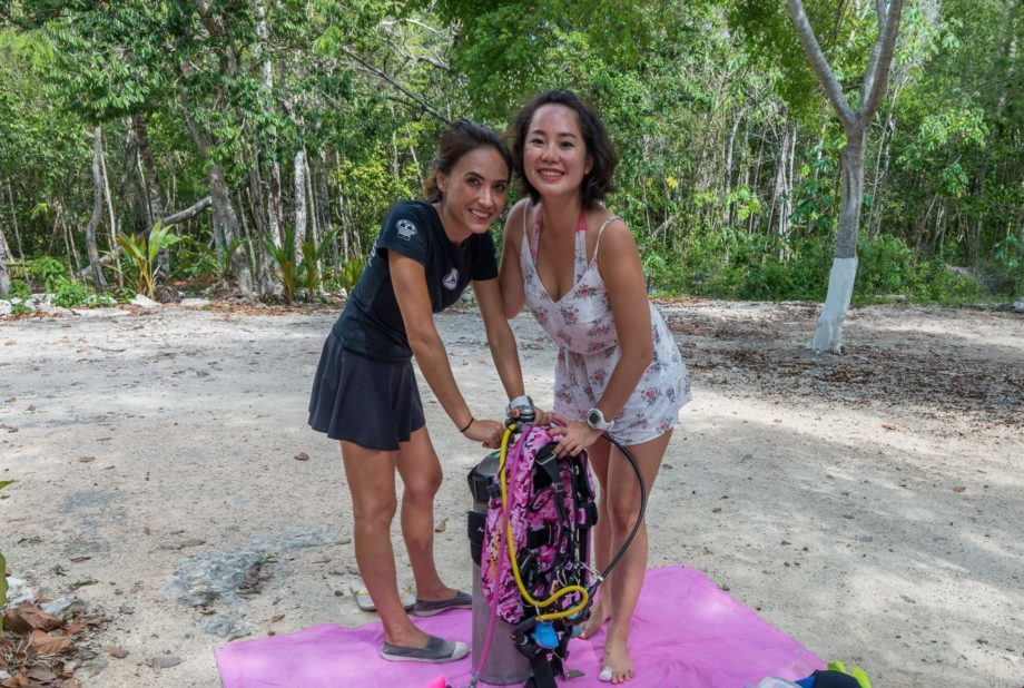 girls that scuba gearing up and cavern diving in a cenote of mexico